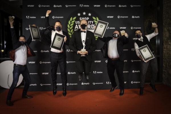 Shop Usability Award 2020: Siegerfoto an der Fotowand mit Johannes Altmann in der Mitte, Gründer von Shoplupe und Initiator des Shop Usability Award
